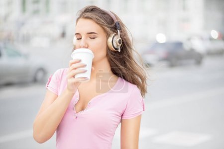 Photo for Beautiful young woman with music headphones, holding a take away coffee cup and listening to the music with her eyes closed against city traffic background. - Royalty Free Image