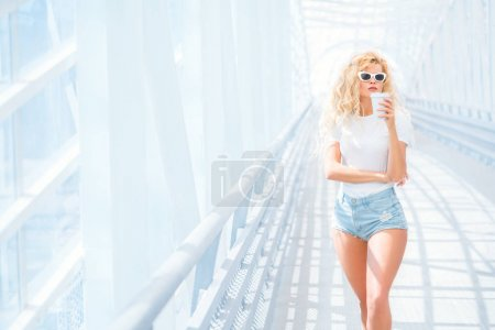 Photo for Thoughtful blonde young woman in sunglasses with take away coffee cup posing on the urban bridge. - Royalty Free Image