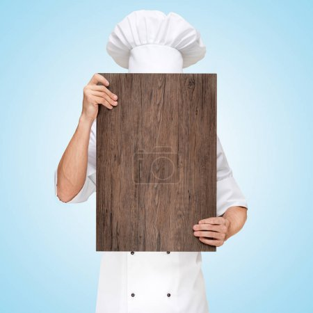 Photo for Restaurant chef hiding behind a wooden chopping board for a business lunch menu with prices. - Royalty Free Image