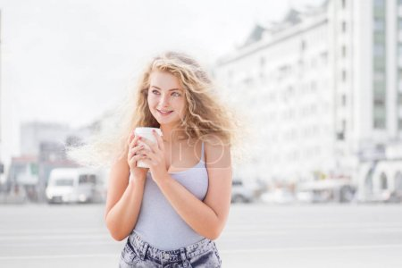 Photo for Happy young woman with long curly hair, holding a take away coffee cup and smiling with flirt in front of a camera against urban city traffic background. - Royalty Free Image