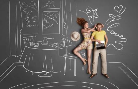 Photo pour Histoire d'amour concept d'un couple romantique sur fond de dessins à la craie. Homme écoutant la musique dans les écouteurs et surfant sur Internet via un ordinateur portable, femme essayant d'attirer son attention . - image libre de droit