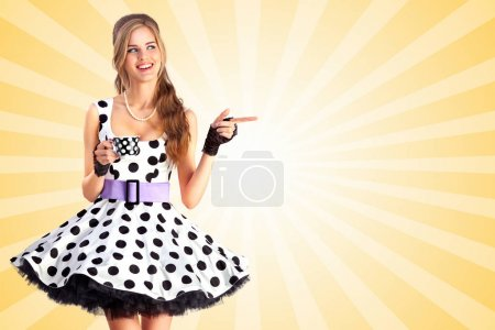 Photo for Creative vintage photo of a beautiful pin-up girl in a polka dot dress, holding a cup of tea and pointing aside on colorful abstract cartoon style background. - Royalty Free Image
