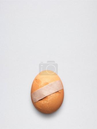 Photo pour Médecine créative et concept de soins de santé, coller du plâtre sur un œuf cassé fissuré . - image libre de droit