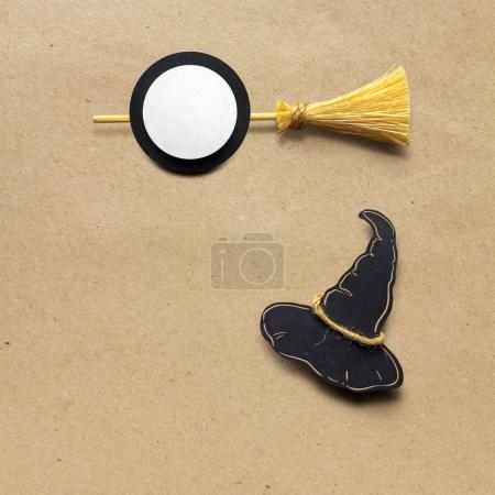 Happy halloween. Creative halloween concept photo of witches hat and broom made of paper on brown background.