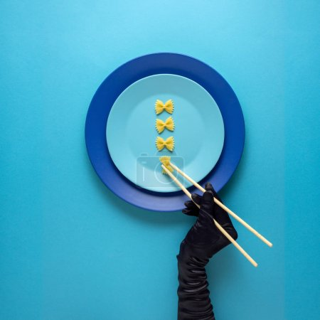 Photo for Creative concept photo of kitchenware with hand, painted plate with food on it on blue background. - Royalty Free Image