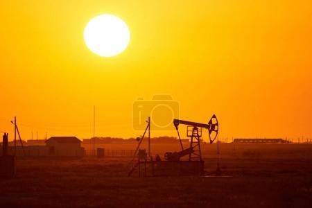 Photo pour Pompage sur fond de coucher de soleil.Un pompage est l'entraînement hors sol pour une pompe à piston alternatif dans un puits de pétrole.L'arrangement est couramment utilisé pour les puits terrestres produisant peu d'huile. Les pompes sont courantes dans les zones riches en pétrole . - image libre de droit