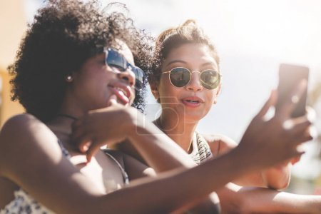 Portrait of two young women looking at smartphone...
