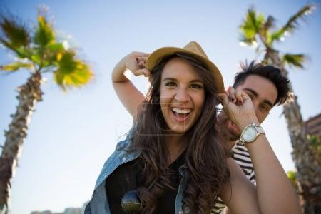 Laughing woman wearing hat and her boyfriend behind her