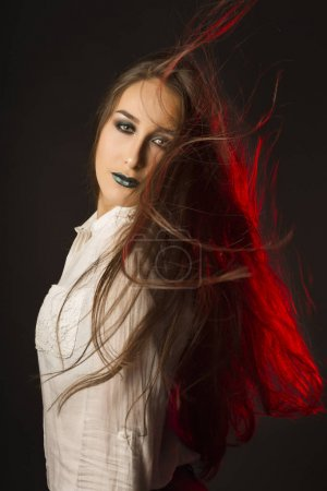 Glamorous woman with wind in hair and dressed in blouse