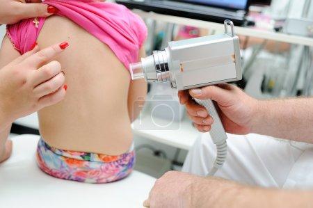 Photo pour Le médecin examine l'enfant de moles de dispositif médical spécial - image libre de droit