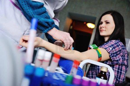 Photo pour Médecin faisant une analyse de sang jeune fille patiente. Échantillonnage sanguin d'une veine sur le fond de la clinique - image libre de droit