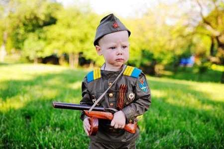 Photo pour Un enfant mignon dans l'uniforme d'un soldat soviétique avec un ruban de St. George avec une arme-jouet sur le fond de la nature. Le 9 mai, le 23 février, défenseur, contre le fascisme. - image libre de droit