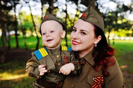 Photo pour Un petit fils avec sa mère dans l'uniforme d'un soldat soviétique dans le contexte de la nature. Le 9 mai, jour de la victoire, la seconde guerre mondiale, la famille, paix, contre le fascisme. - image libre de droit