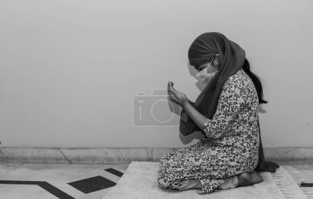 Photo pour Jeune fille priant Namaz en mettant un masque médical et une écharpe sur la tête pour prévenir le virus et les germes - image libre de droit
