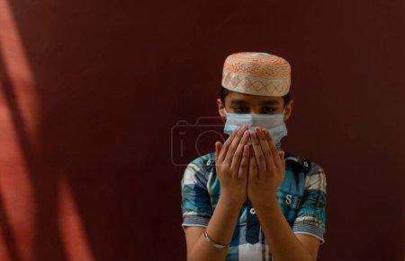 Photo pour Jeune musulman priant Namaz en mettant un masque médical sur son visage - image libre de droit