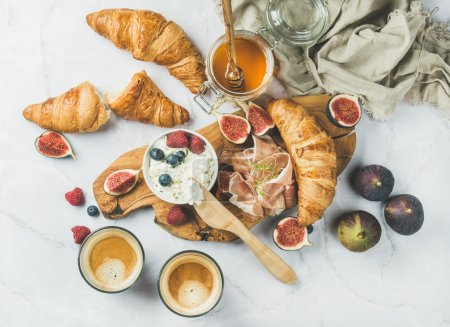 Photo for Breakfast with croissants, homemade ricotta cheese, figs, fresh berries, prosciutto, honey and espresso coffee on rustic serving board over white marble background, top view, horizontal composition - Royalty Free Image