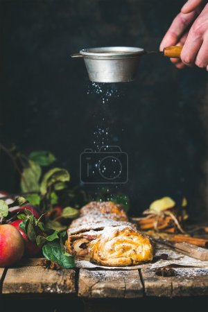 Photo for Apple strudel cake cut in pieces with fresh red apples on rustic wooden table and man's hands with sieve sprinkling sugar powder from above, dark plywood wall background, vertical composition - Royalty Free Image