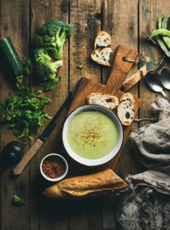 Photo for Homemade pea, broccoli, zucchini cream soup in white bowl with fresh baguette on wooden board over rustic background, top view, vertical composition - Royalty Free Image