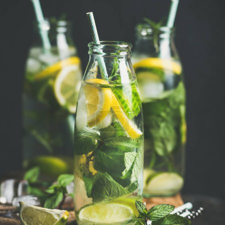 Photo for Citrus fruits and herbs water for detox, healthy eating or dieting in glass bottles with straws, dark background, selective focus - Royalty Free Image