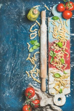 Photo for Ingredients for cooking Italian dinner. Fresh pasta casarecce, tomatoes, basil leaves, bottle of olive oil on colorful wooden board over dark blue background - Royalty Free Image