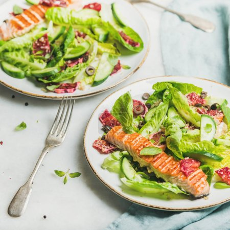 Photo for Healthy energy boosting spring salad with grilled salmon, blood orange, olives and quinoa over grey marble background - Royalty Free Image