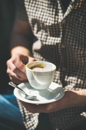 Cup of coffee in man's hands