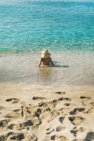 woman lying at clear sea waters