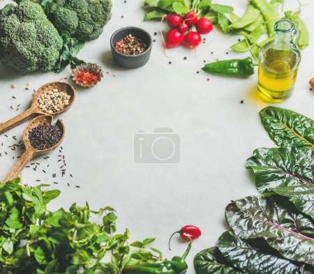 Photo for Fresh raw greens, vegetables, olive oil and grains over light grey marble kitchen countertop, copy space. Healthy, clean eating, vegan, vegetarian, detox, dieting food concept - Royalty Free Image