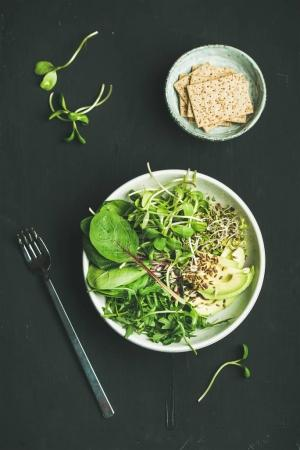 Photo for Green vegan breakfast meal in bowl with spinach, arugula, avocado, seeds and sprouts and crispy bread over black background, top view. Clean eating, dieting, vegan, vegetarian food concept - Royalty Free Image