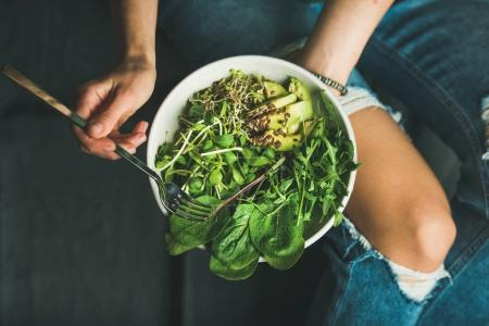 Photo for Green vegan breakfast meal in bowl with spinach, arugula, avocado, seeds and sprouts. Girl in jeans holding fork with knees and hands visible - Royalty Free Image