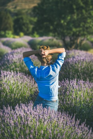 Photo for Young blond curly haired woman traveller wearing straw hat, blue shirt and denim shorts enjoying lavender field surrounded with lavender flowers in Isparta region of Turkey - Royalty Free Image