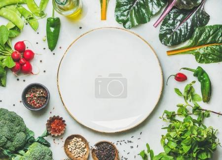 Photo for Fresh raw greens, unprocessed vegetables and grains over light grey marble kitchen countertop, wtite plate in center - Royalty Free Image