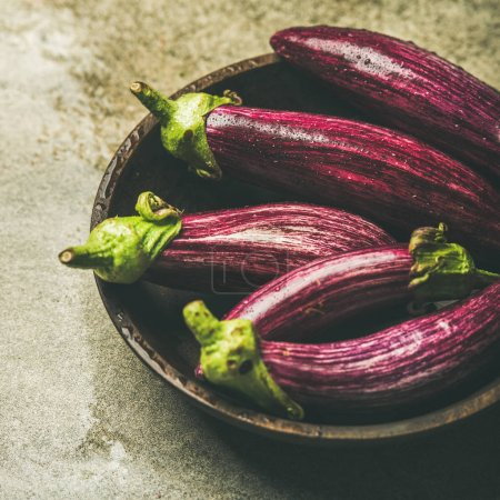 Photo for Fresh raw Fall harvest purple eggplants or aubergines in wooden bowl over grey concrete stone background - Royalty Free Image