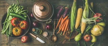 Photo for Fall cooking background. Autumn ingredients for Thanksgiving day dinner preparation. Green beans, corn cobs, carrot, tomatoes, eggplant, fruits over wooden table - Royalty Free Image