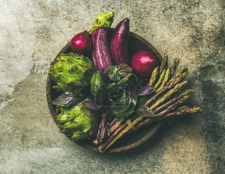 Photo for Green and purple vegetables on plate over grey background, top view. Local produce for healthy cooking - Royalty Free Image