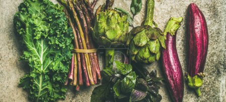 Photo for Green and purple fresh vegetables over concrete background, top view. Local seasonal produce for healthy cooking - Royalty Free Image