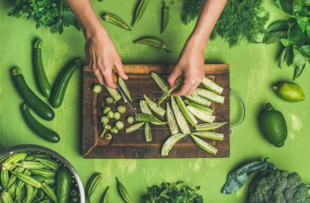 Photo for Healthy vegan cooking ingredients. Flay-lay of woman hands cutting green vegetables and greens on board over wooden green background - Royalty Free Image