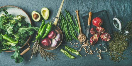 Photo for Winter vegetarian, vegan food cooking ingredients. Seasonal vegetables, fruit, beans, cereals, kitchen utencils, dried flowers, olive oil over grey linen table cloth background - Royalty Free Image