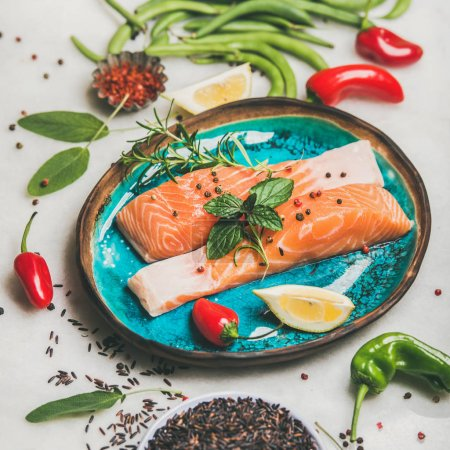Photo for Raw salmon fish fillet steaks with vegetables, greens, rice, spices and lemon in bright blue plate over grey marble background - Royalty Free Image