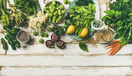 Photo for Spring healthy vegan food cooking ingredients. Vegetables, fruit, seeds, sprouts, flowers, greens over white wooden background - Royalty Free Image