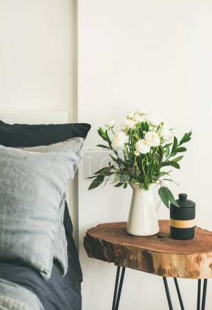 Photo for Trendy Scandinavian style interior shot. Bedroom with washed linen grey pillows and wooden nightstand with bucket of flowers and candle - Royalty Free Image
