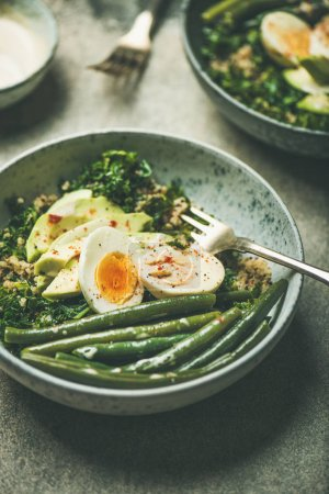 Healthy vegetarian breakfast bowls. Quinoa, kale, green beans, avocado, egg and tahini dressing bowls over concrete background