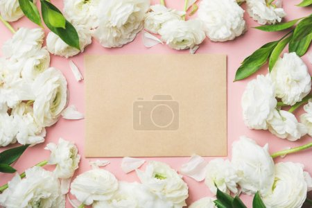 Saint Valentines Day frame or background. White ranunculus flowers and sheet of paper over light pink background