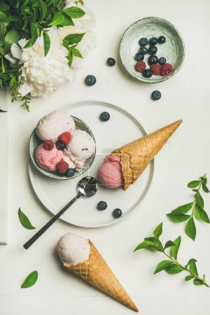 Pink strawberry and coconut ice cream scoops in bowl