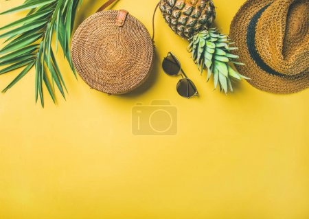 Colorful summer female fashion outfit. Straw hat, bamboo bag, sunglasses, palm branches, fresh pineapple over yellow background