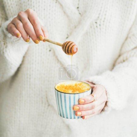 Healthy vegan turmeric latte or golden milk with honey in female hands