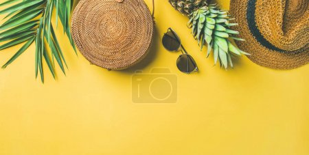 Colorful summer female fashion outfit. Straw hat, bamboo bag, sunglasses, palm branches, pineapple over yellow background