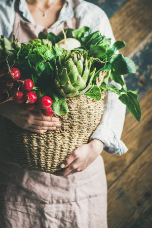 Female farmer wearing pastel linen apron and shirt holding basket with fresh seasonal vegetables in her hands