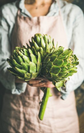 Female farmer wearing pastel linen apron and shirt holding fresh artichokes in her hands