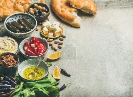 Mediterranean, Middle Eastern meze starter platter. Stuffed pickled paprikas, dolma, hummus, oil, olives, sundried tomatoes, nuts, lemon, flatbread over grey background